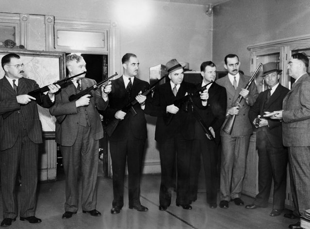 Photo shows Inspector Frank S. Burke, Right, Chief of Detectives, explaining the new weapons to some of his men, left to right, Detectives O. S. Hunt, Thomas Nally, John Apostolides, Robert Barret, Joseph Shinon, Hoyle Secrest, George Darnell and Inspector Burke in Washington, DC on October 19, 1935. (Photo by George Rinhart/Corbis via Getty Images)