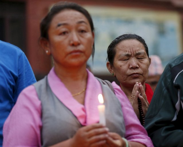 Women pray at a candlelight vigil for victims of the April 25 earthquake in Kathmandu, Nepal, May 7, 2015. (Photo by Olivia Harris/Reuters)