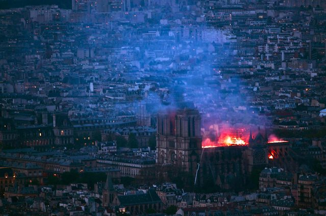 This general view taken from Montparnasse Tower shows flames and smoke as they billow from the roof at Notre-Dame Cathedral in Paris on April 15, 2019. A fire broke out at the landmark Notre-Dame Cathedral in central Paris, potentially involving renovation works being carried out at the site, the fire service said.Images posted on social media showed flames and huge clouds of smoke billowing above the roof of the gothic cathedral, the most visited historic monument in Europe. (Photo by Philippe Lopez/AFP Photo)