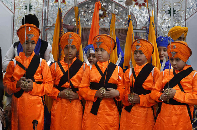 Sikh youth, in traditional dress and holding ceremonial swords, while attending a ceremony during the Vasakhi festival, at the shrine of Gurdwara Punja Sahib, the second most sacred place for Sikhs, in Hasan Abdal, some 50 kilometers (31 Miles) from Islamabad, Pakistan, Sunday, April 14, 2019. Thousands of Sikh pilgrims arrived from neighboring India and other countries to attend the harvest festival that is regionally known by many names and marks the Solar New Year. (Photo by Anjum Naveed/AP Photo)