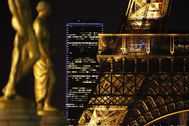 A picture taken from the Trocadero Esplanade shows statues, the Montparnasse Tower (C) and a detail of the Eiffel Tower in Paris on February 13, 2014. (Photo by Ludovic Marin/AFP Photo)