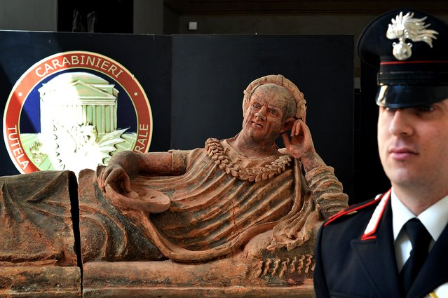 """A Carabiniere stand next to recovered archaeological artifacts in Rome, on March 22, 2016. Italian and Swiss art police have busted open an international art smuggling ring and recovered archaeological artifacts stolen from Italy and destined for sale in Britain, Japan and the United States. Italy's Culture Minister Dario Franceschini said """"45 crates containing tens of thousands of archaeological relics of extraordinary quality"""" were discovered after a joint investigation by Rome and Geneva into looted antiquities. The haul included Etruscan, painted sarcophagi representing human figures, a Roman sarcophagus, marble statues of animals and pieces of the floors and walls of a temple, all dating to between the 7th century BC and 2nd century AD. (Photo by Alberto Pizzoli/AFP Photo)"""
