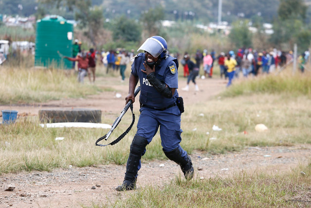 A South African Police Services member reacts after he was hit by a rock during a demonstration of Gomora informal settlement community members to protest against the lack of service delivery or basic necessities such as access to water and electricity, housing difficulties and lack of public road maintenance, on April 11, 2019 in Pretoria. (Photo by Phill Magakoe/AFP Photo)