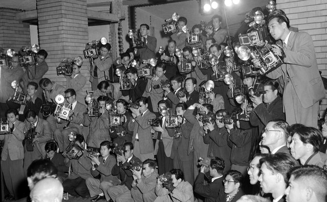 Forty-five cameramen photograph the new Japanese cabinet at the Prime Minister's official residence in downtown Tokyo on December 17, 1954. Japanese newspapers made a practice of assigning three or four photographers to cover an event from all possible angles. (Photo by AP Photo via The Atlantic)