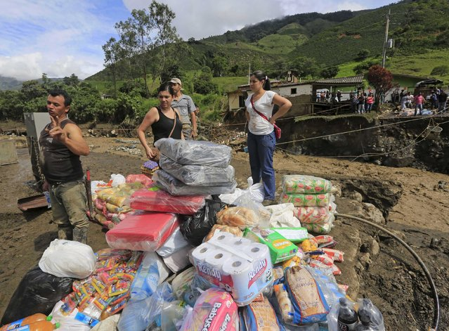 Residents receive supplies after a landslide sent mud and water crashing onto homes close to the municipality of Salgar in Antioquia department, Colombia May 19, 2015. (Photo by Jose Miguel Gomez/Reuters)