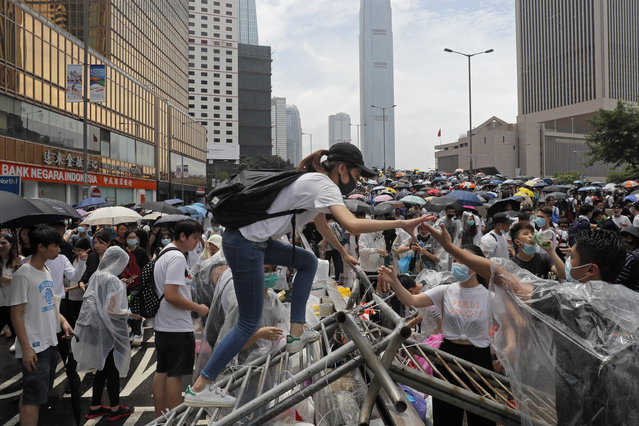 Protestors gather near the Legislative Council in Hong Kong, Wednesday, June 12, 2019. Thousands of protesters blocked entry to Hong Kong's government headquarters Wednesday, delaying a legislative session on a proposed extradition bill that has heightened fears over greater Chinese control and erosion of civil liberties in the semiautonomous territory. (Photo by Kin Cheung/AP Photo)
