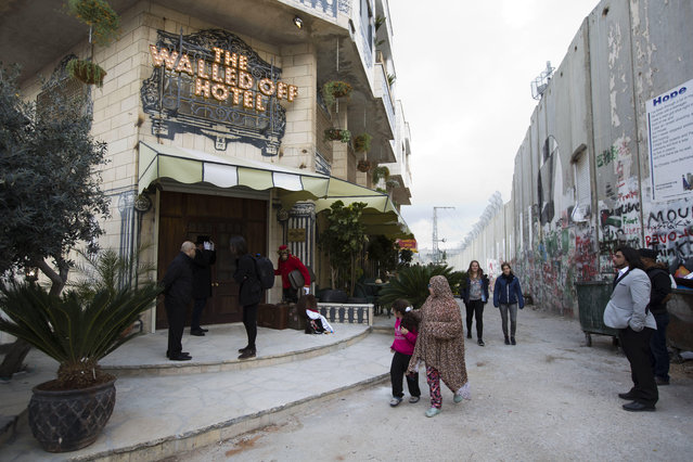 "People pass by the ""The Walled Off Hotel"" and the Israeli security barrier in the West Bank city of Bethlehem, Friday, March 3, 2017. (Photo by Dusan Vranic/AP Photo)"