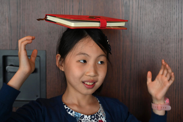 This picture taken on June 1, 2019 shows Danielle Liu balancing a book on her head during an etiquette and manners class in central Shanghai. (Photo by Hector Retamal/AFP Photo)