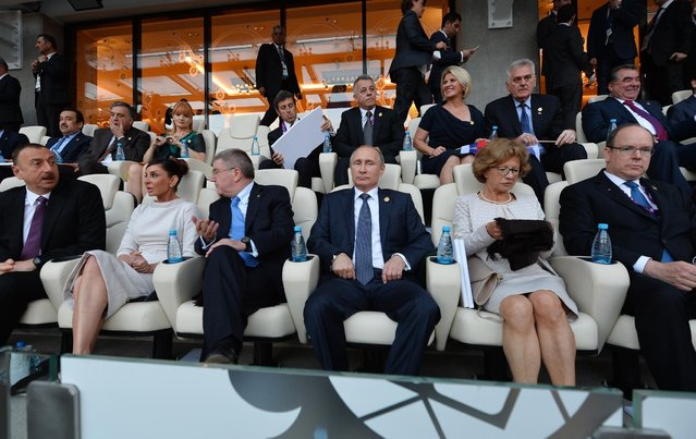 Azerbaijani President Ilham Aliyev, left, his wife Mekhriban, second left, International Olympic Committee (IOC) President Thomas Bach, third left, Russian President Vladimir Putin, center, and Prince Albert II of Monaco, right, during the opening ceremony of the 2015 European Games in Baku, Azerbaijan, Friday, June 12, 2015. (RIA-Novosti, Kremlin Pool Photo via AP)