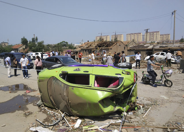Residents past by an overturned car in the aftermath of a tornado in Kaiyuan in northeastern China's Liaoning province Thursday, July 4, 2019. A tornado blew through the city in northeast China, damaging factories and buildings, killing some people and injuring others, state media reported Thursday (Photo by Chinatopix via AP Photo)