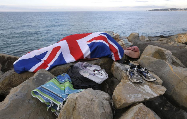 A migrant sleeps on the rocky beach at the Franco-Italian border near Menton, southeastern France Wednesday, June 17, 2015. European Union nations failed to bridge differences Tuesday over an emergency plan to share the burden of the thousands of refugees crossing the Mediterranean Sea, while on the French-Italian border, police in riot gear forcibly removed dozens of migrants. (AP Photo/Lionel Cironneau)