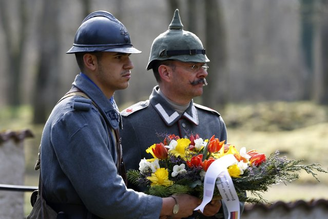 A French, left, and a German member of World War I historical associations lay a wreath for soldiers from both sides who were killed near Bezonvaux. (Photo by Charles Platiau/Reuters)