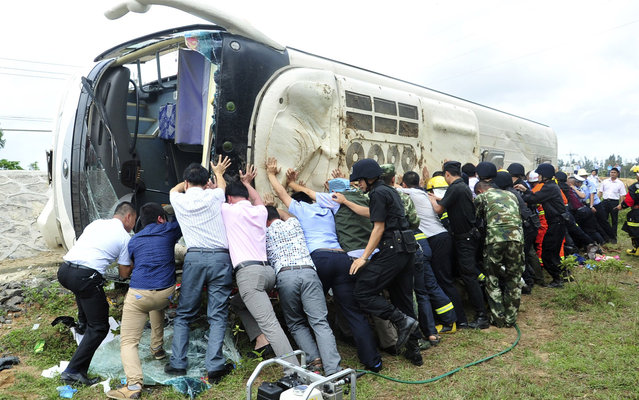Rescuers attempt to push a bus upright, after it overturned while carrying students from a local primary school, next to a street in Wenchang, Hainan province April 10, 2014. Eight school children died in a bus crash on China's southern island province of Hainan on Thursday on their way to a school outing, state media reported. (Photo by Reuters/China Daily)