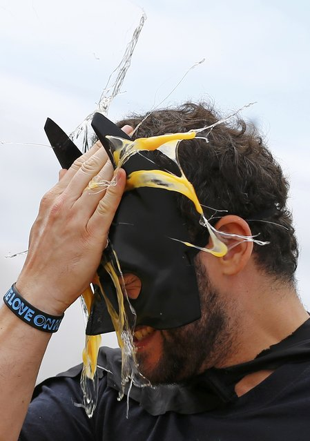 A man wearing a Batman mask loses in a game of Russian Egg Roulette during the World Egg Throwing Championships and Vintage Day in Swaton, Britain June 28, 2015. (Photo by Darren Staples/Reuters)