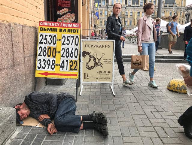 A man sleeps near a display board of a currency exchange office in central Kiev, Ukraine on August 2, 2019. (Photo by Gleb Garanich/Reuters)