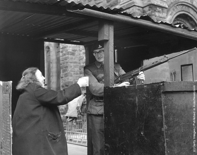1971:  A woman offers a cup of tea to a soldier manning a check point in a Belfast street