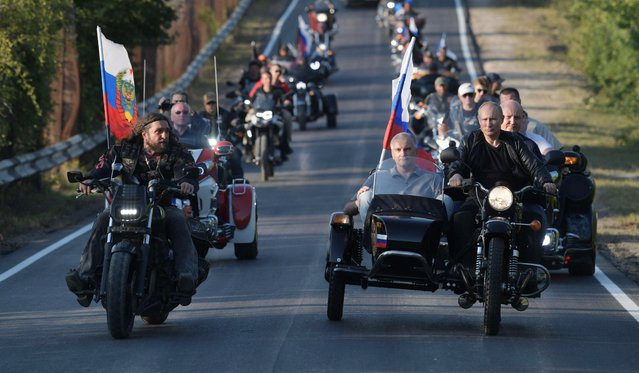 "Russian President Vladimir Putin drives a motorbike, right, as Head of motorcycle club ""Night Wolves"" Alexander Zaldostanov, left, follows him during the Babylon's Shadow bike show camp near in Sevastopol, Crimea, Saturday, August 10, 2019. Head of the Republic of Crimea Sergei Aksenov, is in sidecar, and acting Governor of Sevastopol Mikhail Razvozhaev, rides pillion. (Photo by Alexei Druzhinin/Sputnik/Kremlin/Pool Photo via AP Photo)"