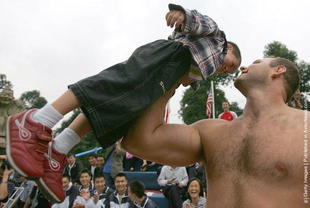 A contestant lifts a Chinese young boy during a match of the 2005 World's Strongest Man Competition at Wuhou Temple