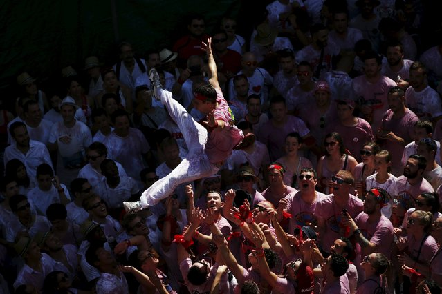 A reveller is tossed in the air during the start of the San Fermin Festival in Pamplona, Spain, July 6, 2015. (Photo by Susana Vera/Reuters)