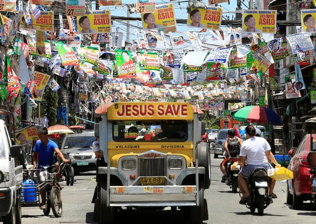 Election posters of Philippine candidates are seen hanging above a jeepney driving along a main street in Pritil, Tondo city, metro Manila in the Philippines May 8, 2016, ahead of the election on Monday. (Photo by Romeo Ranoco/Reuters)