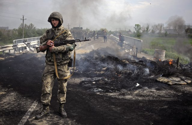 Ukrainian soldiers stay near of a checkpoint seized by them not far of Slaviansk, Ukraine, 02 May 2014. At least three people were killed and several were injured in clashes between Ukrainian forces and pro-Russian separatists in the eastern city of Sloviansk early on 02 May. (Photo by Roman Pilipey/EPA)
