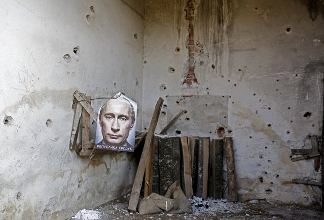 A poster of Russian President Vladimir Putin with the words Republika Srpska (Serb Republic) printed on it is seen inside the main residence of an abandoned agricultural cooperative in Kravica, Bosnia and Herzegovina July 1, 2015. Bullet holes riddle the walls at the site where between 1,000 and 1,500 people were killed, according to the Missing Persons Institute of Bosnia and Herzegovina. (Photo by Dado Ruvic/Reuters)