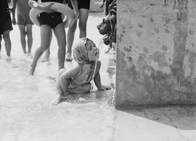 A photograph of a little girl drinking from a fountain with a lion's head at Finchley Swimming Pool, London, taken by Tomlin for the Daily Herald newspaper on 6 August, 1937. (Photo by Daily Herald Archive/SSPL/Getty Images)