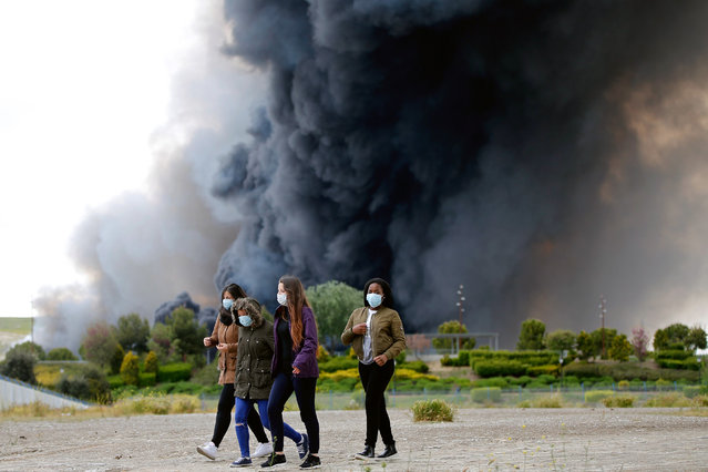 Four women walk with masks in front of billowing black smoke from a huge fire in Sesena, central Spain, Friday, May 13, 2016. A massive fire is raging at a sprawling tire dump in a town near Madrid, sending a spectacular cloud of thick black smoke into the air that's visible for at least 30 kilometers (20 miles). Ten teams of firefighters are trying to put out the blaze at the tire dump in the town of Sesena, still raging more than 10 hours after it started. (Photo by Paul White/AP Photo)
