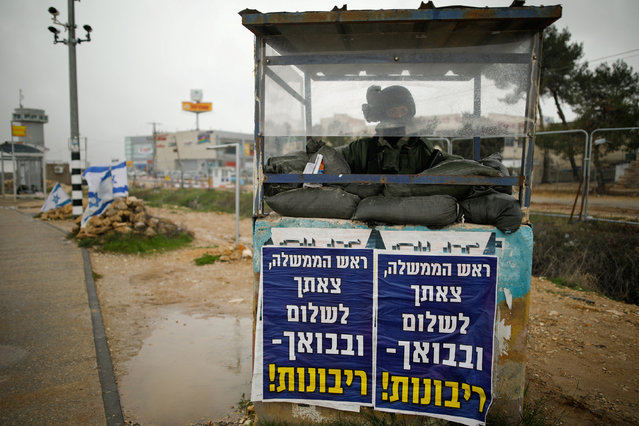 """An Israeli soldier stands inside a guarding booth covered in posters with texts in Hebrew reading """"Prime Minister, we bid you farewell and upon your return – sovereignty!"""" at a junction in the Gush Etzion Israeli settlement block in the occupied West Bank February 15, 2017. (Photo by Amir Cohen/Reuters)"""