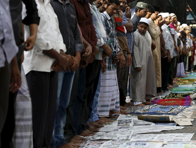 Foreign workers use newspapers for Eid Al-Fitr prayers outside a mosque in Kuala Lumpur, Malaysia, July 17, 2015. (Photo by Olivia Harris/Reuters)