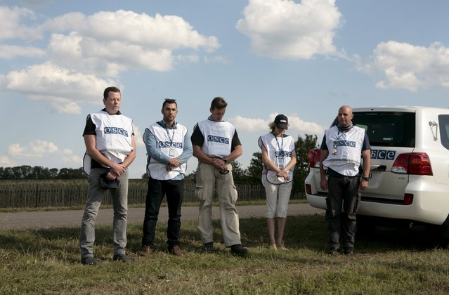 Members of the Organisation for Security and Co-operation in Europe (OSCE) observe a minute of silence at the site of the Malaysia Airlines flight MH17 plane crash near the village of Hrabove in Donetsk region, Ukraine, July 17, 2015. (Photo by Kazbek Basaev/Reuters)