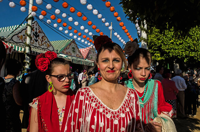 Women wearing traditional Sevillana dresses enjoy the atmosphere at the Feria de Abril (April's Fair) on May 1, 2017 in Seville, Spain. (Photo by David Ramos/Getty Images)