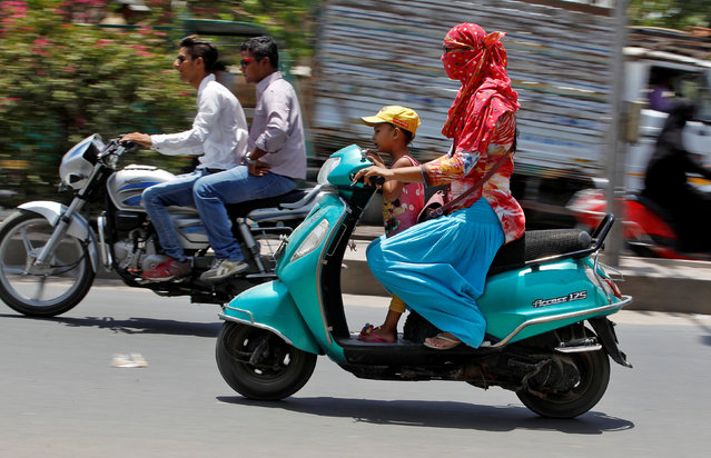 A woman shields her face from the sun as she rides her scooter in Ahmedabad, India May 20, 2016. (Photo by Amit Dave/Reuters)