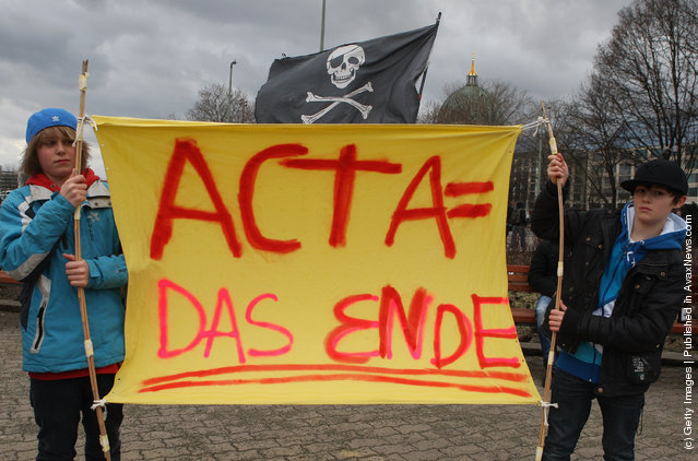 Activists protest from inside the Neptune fountain at Alexanderplatz during a demonstration against the Anti-Counterfeiting Trade Agreement (ACTA)