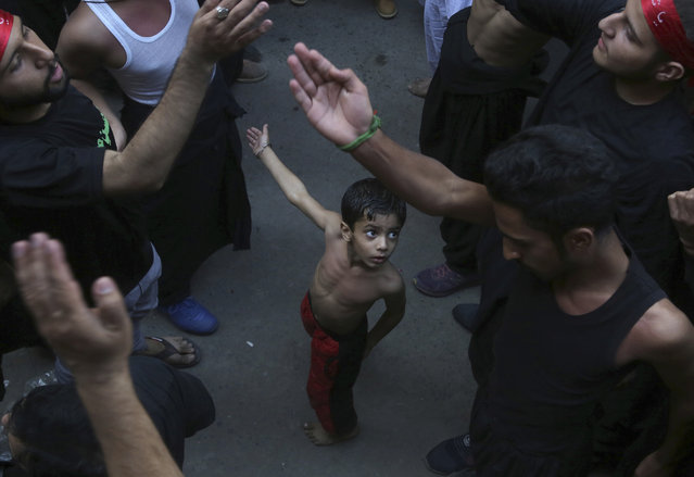 A Shiite Muslim child beats his chest next to his father during a procession to mark the end of the 40 day mourning period following the anniversary of the 7th century death of Imam Hussein, the Prophet Muhammad's grandson and one of Shiite Islam's most beloved saints, in Lahore, Pakistan, Sunday, October 20, 2019. (Photo by K.M. Chaudary/AP Photo)