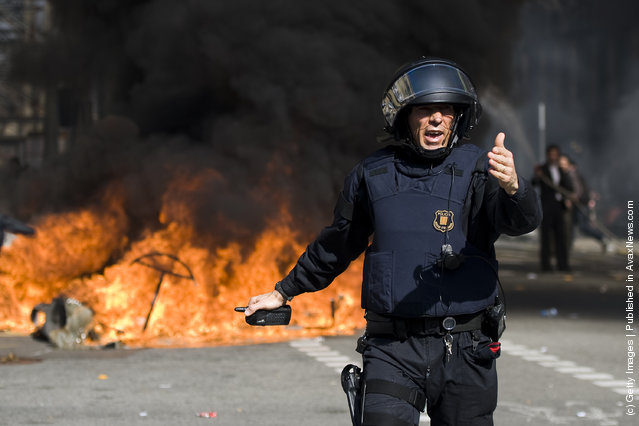 A riot police officer reacts in front of a fire during a university students demonstration on February 29, 2012 in Barcelona