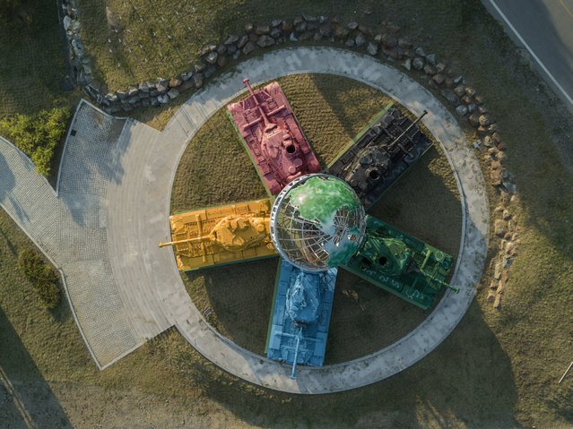 """A photo taken on May 21, 2017 shows an aerial view of an art installation featuring Korean war-era tanks painted in different colours around a globe with a slogan reading: """"Peace All Around the World"""", at the Peace dam, north of Hwacheon near the Demilitarized Zone (DMZ) separating North and South Korea. Contruction of the 'Peace Dam' was intermittent from 1987 to 2005, reportedly as a response to the threat of accidental or intentional flooding from the North Korea's Imnam Dam which lies further up river, across the DMZ. North Korea on May 22 confirmed the """"successful"""" launch of a medium-range ballistic missile, Pyongyang's state media reported, adding the weapon was now ready to be deployed for military action. (Photo by Ed Jones/AFP Photo)"""