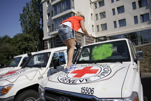 A demonstrator uses spray-paint to deface the windshield of a car of the OSCE and the International Committee of the Red Cross during a protest in Donetsk, eastern Ukraine, Thursday, July  23, 2015. Observers at the Organization for Security and Cooperation and Security in Europe say protesters in rebel-controlled Donetsk vandalized their cars on Thursday showed several dozen protesters outside the hotel where OSCE observers were staying. (Photo by Alexander Ermochenko/AP Photo)