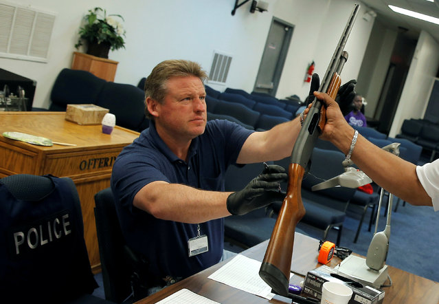 "A Chicago Police officer is handed a shotgun to catalog that was turned in from the public as part of the ""Gun Turn-in"" event where a gift card is given for every firearm turned over to police at Universal Missionary Baptist Church in Chicago, Illinois, U.S. May 28, 2016. (Photo by Jim Young/Reuters)"