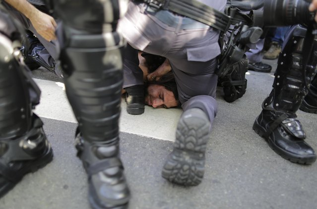 A protester is detained by police during a demonstration demanding better public services and protesting the money spent on the World Cup soccer tournament in Sao Paulo, Brazil, Thursday, June 12, 2014. Brazilian police clashed with anti-World Cup protesters trying to block part of the main highway leading to the stadium that hosts the opening match of the tournament. (Photo by Nelson Antoine/AP Photo)