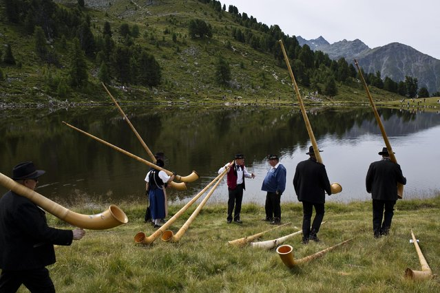 Alpenhorn players carry their instruments as they walk along the Lac de Tracouet, situated 2200 meters (7220 feet) above sea level in Haute-Nendaz, canton of Valais, Switzerland, Sunday, July 26, 2015. More than 200 alpenhorn players gathered in Nendaz on Sunday to perform as an ensemble in the Alpenhorn Festival. (Photo by David Azia/AP Photo)