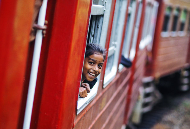 """""""Travelling Girl"""". She was shy at first and barely visible peering out the window, I simply waved and smiled and we shared many small moments and giggles. If I am able to somehow express how incredible the Sri Lankan people are it can be seen through this girl's smile. Photo location: Hatton, Sri Lanka. (Photo and caption by Ante Badzim/National Geographic Photo Contest)"""