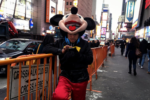 A man wearing a Mickey Mouse costume and who poses for photos for tips sends a text message while standing in Times Square in the Manhattan borough of New York, U.S., April 29, 2016. (Photo by Carlo Allegri/Reuters)