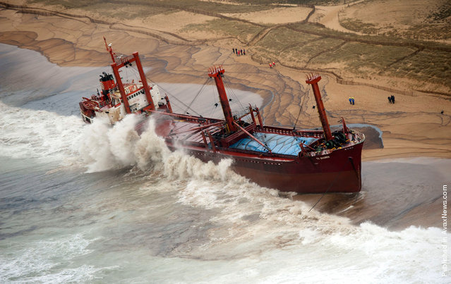 In this image made available by France's Marine Nationale, the cargo ship TK Bremen sits stranded on a beach near Erdeven, France, on December 16, 2011, spilled fuel oil fouling the water