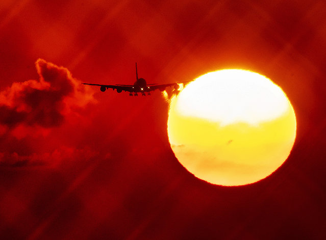 In this Wednesday, August 21, 2019 file photo, an aircraft passes the rising sun as it approaches the airport in Frankfurt, Germany. The European Union says it will miss its targets for reducing planet-warming greenhouse gases by 2030 unless member states make a greater effort than they have so far. (Photo by Michael Probst/AP Photo/File)