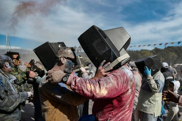 """Revellers use old TVs as masks as they participate in a """"flour war"""" during """"Ash Monday"""" celebration, a traditional festivity marking the end of the carnival season and the start of the 40-day Lent period until the Orthodox Easter, in the port town of Galaxidi, Greece, on March 11, 2019. (Photo by Aris Messinis/AFP Photo)"""