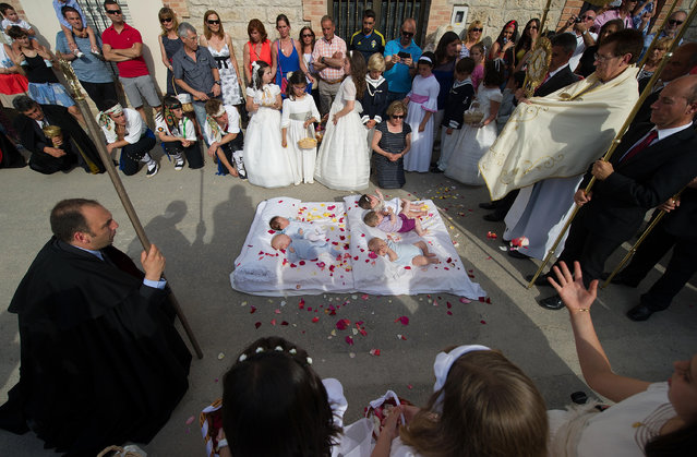 Babies, covered in confetti are blessed during el Salto del Colacho (the devil's jump) festival on June 22, 2014 in Castrillo de Murcia, Spain. The festival, held on the first Sunday after Corpus Cristi, is a catholic rite of the devil cleansing babies of original sin by jumping over them. (Photo by Denis Doyle/Getty Images)