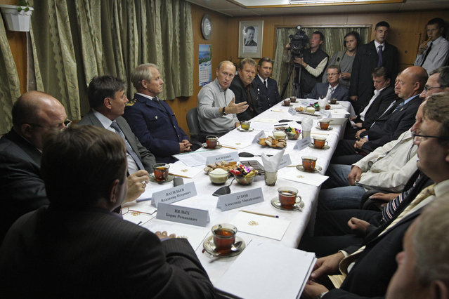 Prime Minister Vladimir Putin,  4th from left, speaks with the crew of the Mikhail Stanitsyn refrigerating trawler while visiting the ship anchored at Petropavlovsk-Kamchatsky harbor, the regional capital of  Russia's Pacific Kamchatka peninsula, Tuesday, August 24, 2010. Putin is on a trip around East Siberia and the Far East, the state news agency ITAR-Tass reported. (Photo by Alexei Druzhinin/AP Photo/RIA Novosti)
