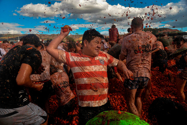 """People participate in the tenth annual tomato fight festival, known as """"Tomatina"""", in Sutamarchan, Boyaca department, Colombia, on June 2, 2019. (Photo by Diana Sanchez/AFP Photo)"""