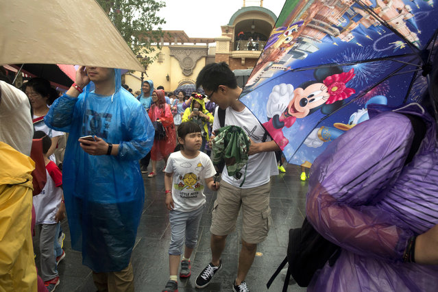 Visitors arrive on the opening day of the Disney Resort in Shanghai, China, Thursday, June 16, 2016. (Photo by Ng Han Guan/AP Photo)
